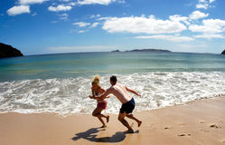 Couple play on empty beach in New Zealand Royalty Free Stock Photos