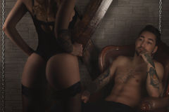 Couple play in love games. BDSM. dominatrix woman in sexy black lingerie stand beside man in chair. male watching Stock Photo