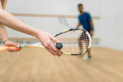 Couple play squash game in indoor training club. Young couple with rackets play squash game in indoor training club. Active sport lifestyle. Recreation workout Stock Photos