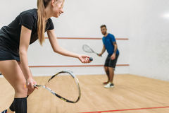 Couple play squash game in indoor training club. Young couple with rackets play squash game in indoor training club. Active sport lifestyle. Recreation workout Stock Photo