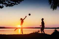 Couple in play at sunset by the lake Stock Image