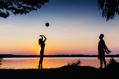 Couple in play at sunset by the lake Royalty Free Stock Photo