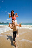 Couple playful by the beach. A happy couple having lots of fun at the beach Stock Photography