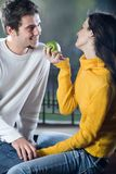 Couple playfully eating apple. Happy yound couple playfully eating apple Royalty Free Stock Photos