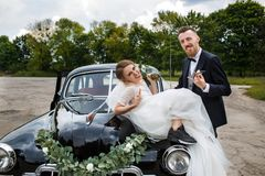 Couple playfully posing sitting on a retro car stock photography