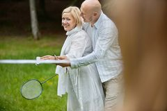 Couple Playing Badminton Together. Portrait of mature couple in casual wear playing badminton together on a weekend outing Stock Image