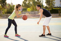 Couple playing basketball outdoors stock photos
