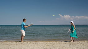 Couple playing bat and ball at the beach. Couple playing bat and ball tennis game at the beach on the golden sand at the edge of a calm ocean as they enjoy their stock footage