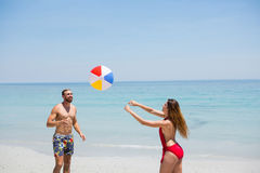 Couple playing with beach ball. On shore against clear sky Stock Images
