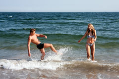 Couple playing in beach water. Beautiful young couple playing in the ocean at the beach splashing water, heaving fun on a summer day stock photo