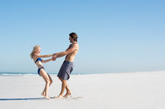 Couple playing at beach stock photo