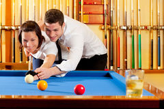 Couple playing billiard expertise teacher. And beautiful girl stock photography