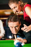 Couple playing billiards stock images