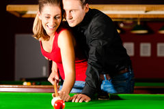 Couple playing billiards Stock Image
