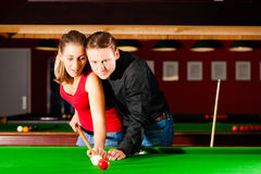 Couple playing billiards Stock Photo