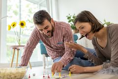 Couple playing board games at home. Couple in love enjoying their time together, eating popcorn and having fun while playing ludo board game stock photos
