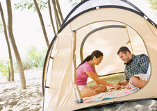 Couple playing boardgame in tent royalty free stock photography