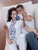 Couple playing with a camera in living-room Stock Images