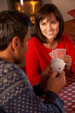 Couple Playing Cards By Cosy Log Fire. Smiling Royalty Free Stock Photo
