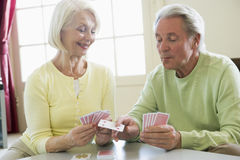 Couple playing cards in living room smiling Stock Photo
