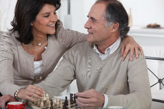 Couple playing chess Stock Photos