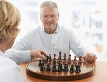Couple playing chess in living room Stock Photo