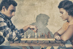 Couple playing chess Stock Images