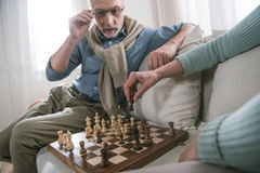 Couple playing chess while sitting on sofa at home Stock Photography
