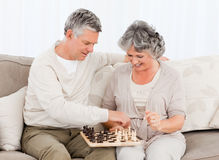 Couple playing chess on their sofa stock images
