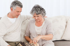 Couple playing chess on their sofa Royalty Free Stock Image