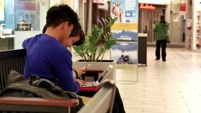 Couple playing computer and cellphone at resting area stock video footage