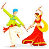 Couple playing Dandiya Stock Images