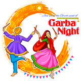 Couple playing Dandiya in disco Garba Night poster for Navratri Dussehra festival of India Royalty Free Stock Image