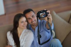 Couple playing with digital camera at home Royalty Free Stock Images