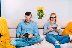 Couple playing digital video games with joystick controller while sitting on sofa or couch. Stock Image