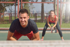 Couple playing doubles at the tennis court Stock Photo