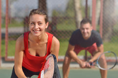 Couple playing doubles at the tennis court. Smiling woman at first plane. Royalty Free Stock Photo
