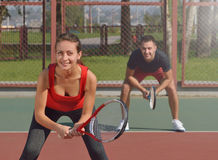 Couple playing doubles at the tennis court. Waiting for second serve. Royalty Free Stock Photo