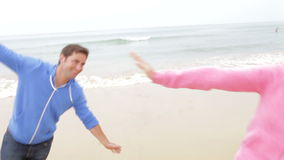 Couple Playing On Fall Beach Together. Couple running up beach towards camera with arms stretched pretending to be aeroplanes.Shot on Canon 5D Mk2 at at a frame stock footage