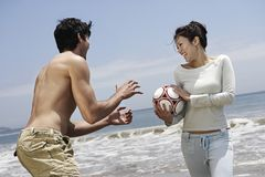 Couple Playing With Football On Beach. Happy middle aged couple playing with football on beach Royalty Free Stock Photos