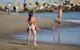 Couple playing frisbee. On the beach Stock Photo