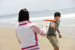 Couple Playing Frisbee On Beach. Happy couple playing Frisbee on beach during vacation Stock Photo