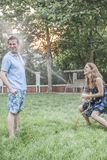 Couple playing with a garden hose and spraying each other outside in the garden Stock Photos