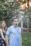Couple playing with a garden hose and spraying each other outside in the garden, man has a shocked look. Couple playing with a garden hose and spraying each royalty free stock photo