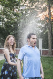 Couple playing with a garden hose and spraying each other outside in the garden, man has a shocked look. Couple playing with a garden hose and spraying each stock images