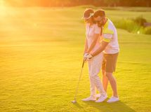Couple playing golf. Beautiful young couple is hugging and smiling while playing golf Stock Photos