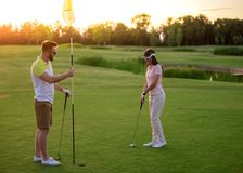 Couple playing golf. Beautiful young couple is using golf clubs while playing golf together Royalty Free Stock Photography