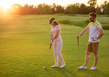 Couple playing golf. Beautiful young couple is using golf clubs while playing golf together Royalty Free Stock Images