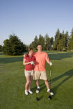 Couple Playing Golf on Course - Vertical Royalty Free Stock Image