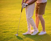 Couple playing golf. Cropped image of beautiful young couple hugging while playing golf Royalty Free Stock Photo